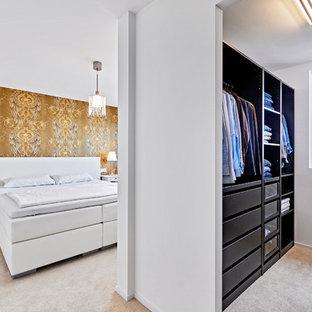 Ejemplo de armario vestidor de hombre, actual, de tamaño medio, con armarios con paneles lisos, puertas de armario negras y moqueta