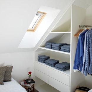 Cette image montre un placard dressing design de taille moyenne pour un homme avec un placard à porte plane et des portes de placard blanches.