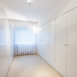 Inspiration for a mid-sized contemporary ceramic floor and beige floor reach-in closet remodel in Frankfurt with flat-panel cabinets and white cabinets