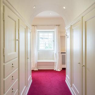 Diseño de armario de mujer, clásico, de tamaño medio, con armarios con paneles empotrados, puertas de armario blancas, moqueta y suelo rosa