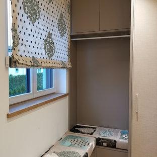 Modelo de vestidor nórdico, grande, con armarios con paneles lisos, puertas de armario beige y suelo de madera clara