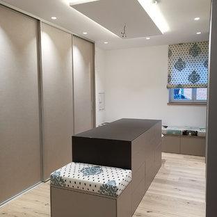 Modelo de vestidor escandinavo, grande, con armarios con paneles lisos, puertas de armario beige y suelo de madera clara