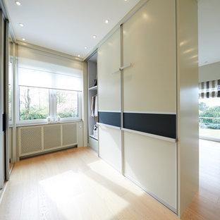 Ejemplo de vestidor unisex, actual, de tamaño medio, con armarios con paneles lisos, puertas de armario amarillas, suelo de madera clara y suelo beige