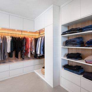 Neutraler, Großer Moderner Begehbarer Kleiderschrank mit Schrankfronten mit vertiefter Füllung, weißen Schränken, Betonboden und grauem Boden in München