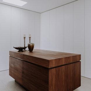 Modern inredning av ett stort omklädningsrum för könsneutrala, med släta luckor, vita skåp, kalkstensgolv och grått golv