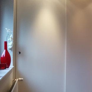 Modelo de armario unisex, actual, de tamaño medio, con armarios con paneles lisos, puertas de armario blancas, suelo laminado y suelo marrón