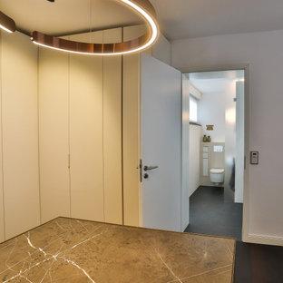 Idées déco pour un grand dressing contemporain neutre avec un placard à porte plane, des portes de placard en bois sombre, un sol en ardoise, un sol noir et un plafond en papier peint.