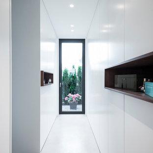 Idee per un grande spazio per vestirsi unisex minimalista con ante lisce, ante bianche, pavimento in cemento e pavimento grigio