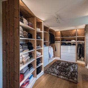 Ejemplo de armario vestidor unisex, rústico, de tamaño medio, con armarios abiertos, puertas de armario de madera oscura, suelo de madera en tonos medios y suelo marrón