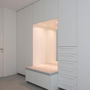 Ispirazione per uno spazio per vestirsi unisex minimal di medie dimensioni con ante lisce, ante bianche e pavimento in cemento