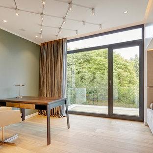 Foto di un ufficio minimal di medie dimensioni con pareti verdi, parquet chiaro, nessun camino, scrivania autoportante e pavimento beige