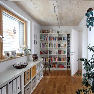 Mittelgroßes Modernes Lesezimmer mit weißer Wandfarbe, braunem Holzboden und braunem Boden in München