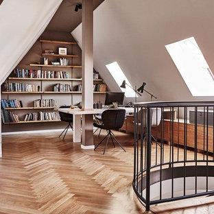 Großes Nordisches Arbeitszimmer ohne Kamin mit Arbeitsplatz, weißer Wandfarbe, braunem Holzboden, freistehendem Schreibtisch und braunem Boden in Berlin