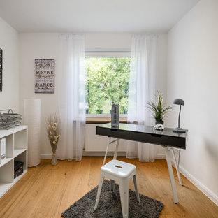 Mittelgroßes Klassisches Arbeitszimmer mit Arbeitsplatz, weißer Wandfarbe, braunem Holzboden, freistehendem Schreibtisch und braunem Boden in München