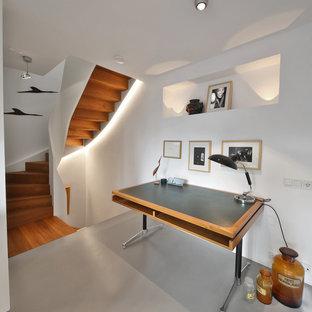 Mittelgroßes Modernes Arbeitszimmer ohne Kamin mit Arbeitsplatz, weißer Wandfarbe, Betonboden, freistehendem Schreibtisch und grauem Boden in München