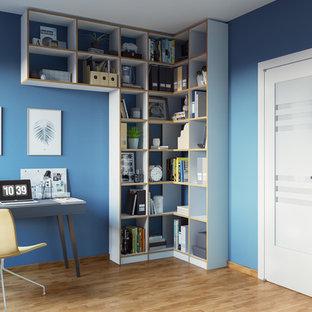 Пример оригинального дизайна: рабочее место в современном стиле с синими стенами, деревянным полом, подвесным камином, отдельно стоящим рабочим столом и коричневым полом