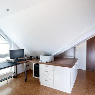 エッセンの中くらいのコンテンポラリースタイルのおしゃれな書斎 (白い壁、コルクフローリング、造り付け机、茶色い床) の写真