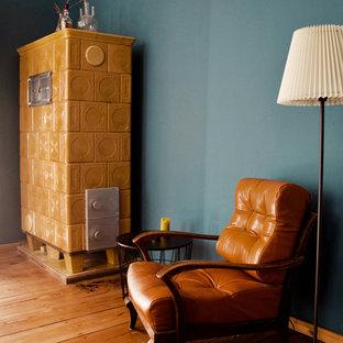 Ispirazione per un grande studio minimalista con libreria, pareti blu, pavimento in legno massello medio, stufa a legna, cornice del camino piastrellata, scrivania autoportante e pavimento marrone