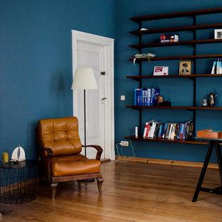 Immagine di un grande studio minimalista con libreria, pareti blu, pavimento in legno massello medio, stufa a legna, cornice del camino piastrellata, scrivania autoportante e pavimento marrone