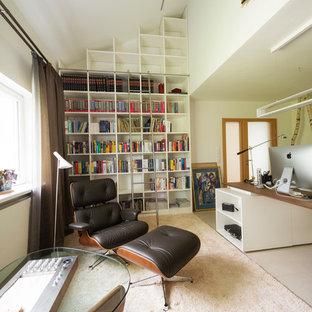 Modernes Arbeitszimmer ohne Kamin mit Arbeitsplatz, weißer Wandfarbe, freistehendem Schreibtisch und beigem Boden in Nürnberg