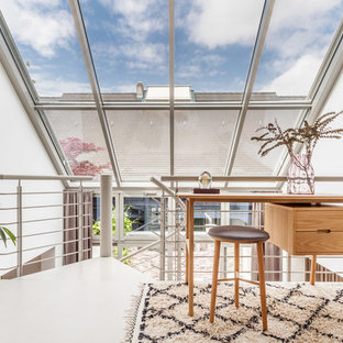 Kleines Modernes Arbeitszimmer ohne Kamin mit Arbeitsplatz, weißer Wandfarbe, Betonboden, freistehendem Schreibtisch und grauem Boden in Sonstige
