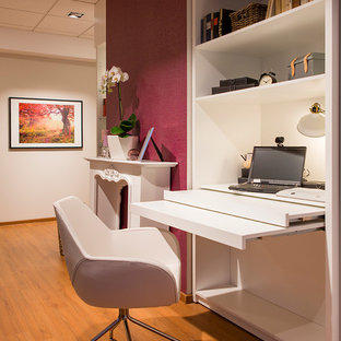 Example of a trendy built-in desk light wood floor home studio design in Berlin with white walls and a standard fireplace