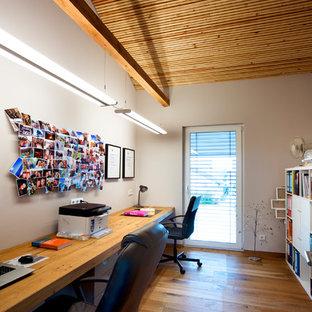 Mittelgroßes Landhausstil Arbeitszimmer ohne Kamin mit Arbeitsplatz, weißer Wandfarbe, braunem Holzboden, Einbau-Schreibtisch und braunem Boden in Nürnberg