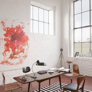 Mittelgroßes Industrial Arbeitszimmer ohne Kamin mit Arbeitsplatz, weißer Wandfarbe, Betonboden, freistehendem Schreibtisch und rotem Boden in Berlin