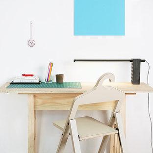 Idee per uno studio industriale di medie dimensioni con libreria, pareti bianche, parquet scuro, camino sospeso, cornice del camino in metallo, scrivania autoportante e pavimento marrone