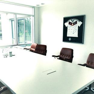 ケルンの巨大なコンテンポラリースタイルのおしゃれな書斎 (白い壁、ラミネートの床、自立型机、茶色い床) の写真