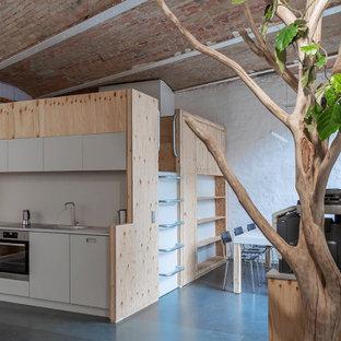 Foto de despacho abovedado y ladrillo, minimalista, de tamaño medio, ladrillo, con paredes blancas, suelo de linóleo, escritorio empotrado, suelo gris y ladrillo