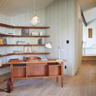 サンフランシスコの広いミッドセンチュリースタイルのおしゃれなホームオフィス・書斎 (ライブラリー、グレーの壁、淡色無垢フローリング、自立型机、表し梁、パネル壁) の写真