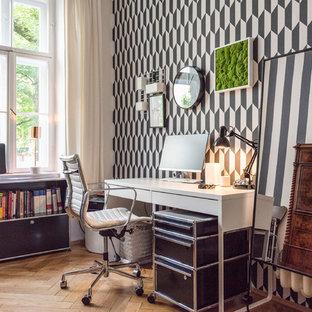 Mittelgroßes Modernes Arbeitszimmer mit Arbeitsplatz, bunten Wänden, braunem Holzboden, braunem Boden und freistehendem Schreibtisch in München