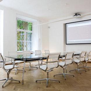 Esempio di un ufficio minimal di medie dimensioni con pareti verdi, scrivania autoportante, pavimento grigio, parquet chiaro, nessun camino e cornice del camino in cemento