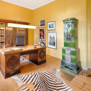 ハノーファーの中くらいのエクレクティックスタイルのおしゃれな書斎 (黄色い壁、塗装フローリング、薪ストーブ、タイルの暖炉まわり、自立型机、茶色い床) の写真