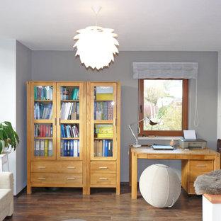 Mittelgroßes Modernes Arbeitszimmer mit Arbeitsplatz, grauer Wandfarbe, braunem Holzboden, Kamin, freistehendem Schreibtisch und braunem Boden in Dresden