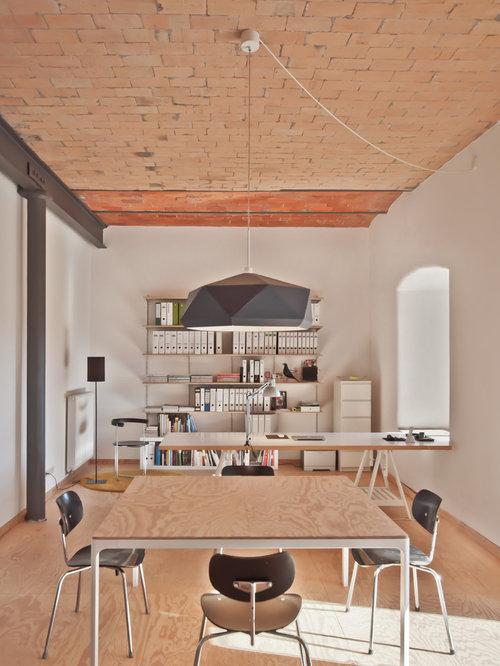 Mittelgroßes Nordisches Arbeitszimmer Mit Arbeitsplatz, Weißer Wandfarbe,  Braunem Holzboden, Freistehendem Schreibtisch Und Braunem