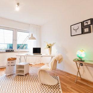 Mittelgroßes Nordisches Arbeitszimmer ohne Kamin mit Arbeitsplatz, weißer Wandfarbe, braunem Holzboden, freistehendem Schreibtisch und beigem Boden in Sonstige