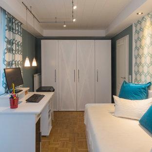 ミュンヘンの小さいコンテンポラリースタイルのおしゃれなホームオフィス・書斎 (ライブラリー、青い壁、淡色無垢フローリング、自立型机、黄色い床) の写真