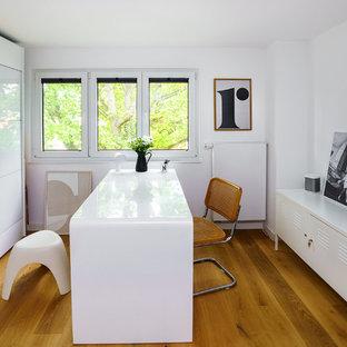 Großes Modernes Arbeitszimmer ohne Kamin mit Arbeitsplatz, weißer Wandfarbe, braunem Holzboden, freistehendem Schreibtisch und braunem Boden in Frankfurt am Main