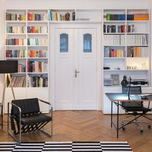 ベルリンの巨大なコンテンポラリースタイルのおしゃれなホームオフィス・書斎 (白い壁、無垢フローリング、ベージュの床、ライブラリー、暖炉なし、自立型机) の写真