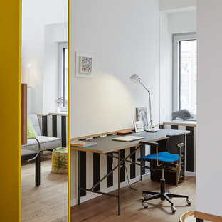 Kleines Modernes Arbeitszimmer ohne Kamin mit Arbeitsplatz, weißer Wandfarbe, hellem Holzboden, freistehendem Schreibtisch und braunem Boden in Düsseldorf