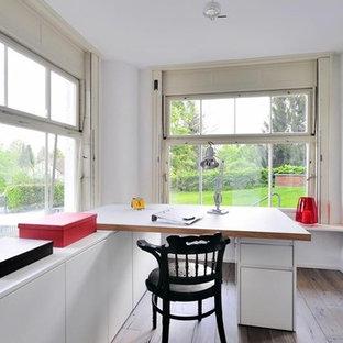 Ejemplo de despacho minimalista, grande, sin chimenea, con paredes blancas, suelo de madera en tonos medios, escritorio empotrado, marco de chimenea de yeso y suelo marrón
