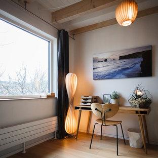 Mittelgroßes Skandinavisches Arbeitszimmer ohne Kamin mit Arbeitsplatz, weißer Wandfarbe, hellem Holzboden, freistehendem Schreibtisch und braunem Boden in Berlin
