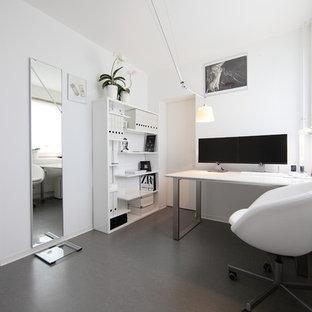 Пример оригинального дизайна: маленькое рабочее место в стиле модернизм с белыми стенами, отдельно стоящим рабочим столом и полом из линолеума без камина