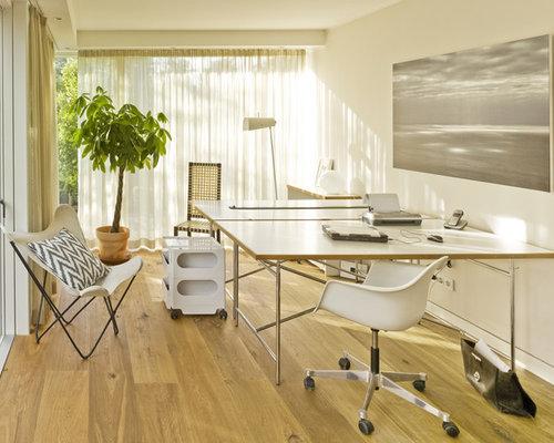 Großes Modernes Arbeitszimmer Ohne Kamin Mit Arbeitsplatz, Weißer  Wandfarbe, Hellem Holzboden Und Freistehendem Schreibtisch
