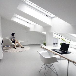 Modern inredning av ett arbetsrum, med vita väggar, linoleumgolv, ett fristående skrivbord och grått golv