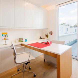 Mittelgroßes Modernes Arbeitszimmer ohne Kamin mit Arbeitsplatz, weißer Wandfarbe, braunem Holzboden, Einbau-Schreibtisch und beigem Boden in Düsseldorf