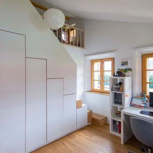 Landhaus Arbeitszimmer mit weißer Wandfarbe, braunem Holzboden, freistehendem Schreibtisch, braunem Boden und gewölbter Decke in München