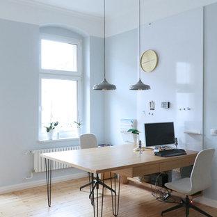 Großes Skandinavisches Arbeitszimmer ohne Kamin mit Arbeitsplatz, blauer Wandfarbe, hellem Holzboden, Einbau-Schreibtisch und beigem Boden in Berlin